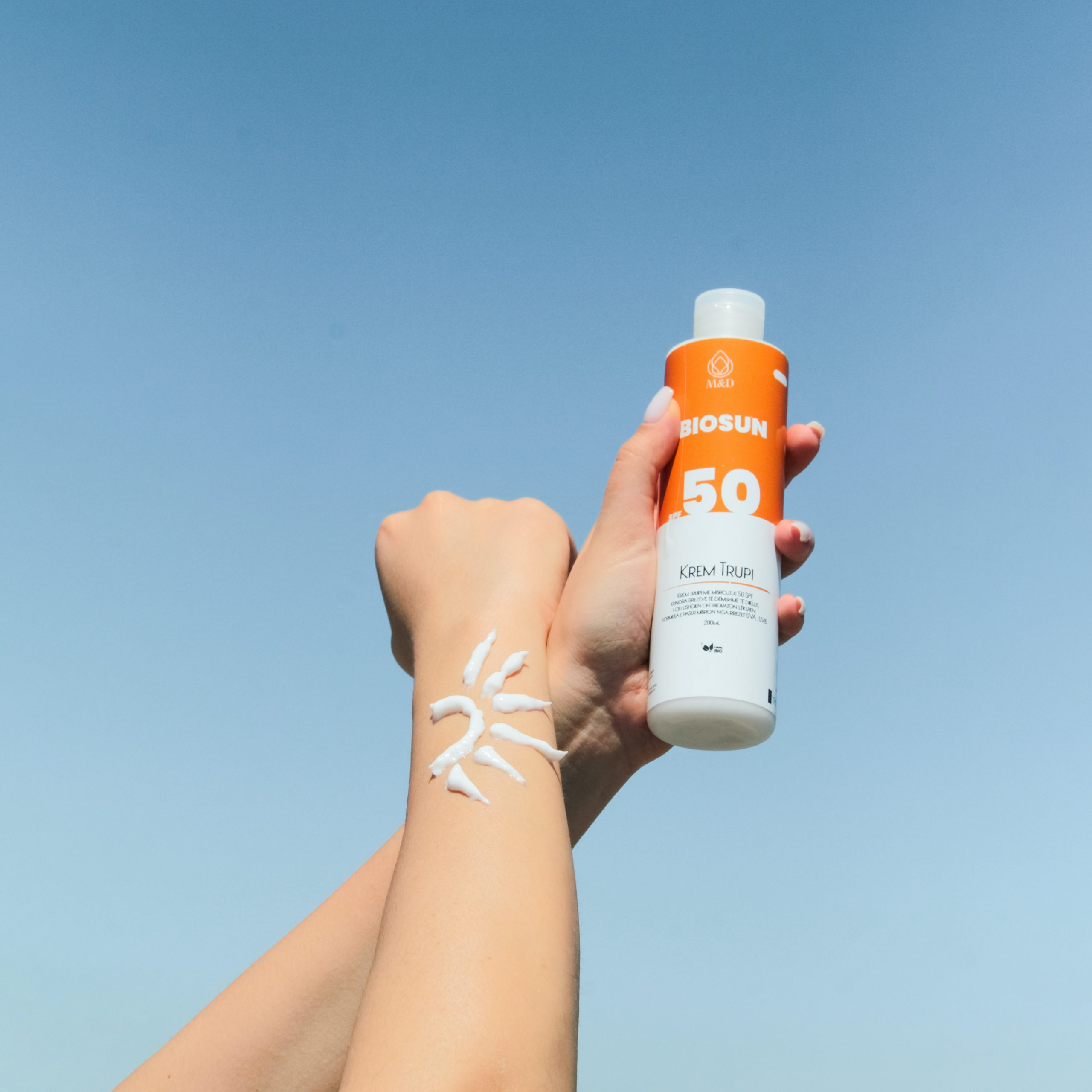 arm with sunscreen applied in sun design and hand holding sunscreen bottle